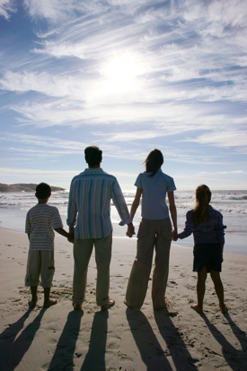 Young Couple with Two Children (8-12) Walking on the Beach